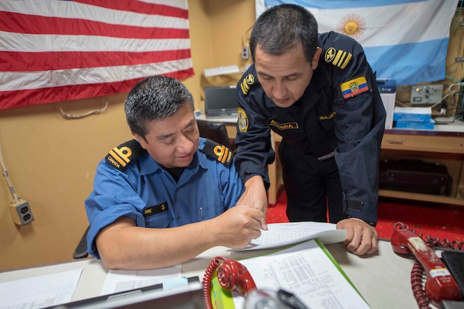 A Royal Canadian Navy officer and an Ecuadorian Navy officer review a schedule of events while aboard USS Gunston Hall.