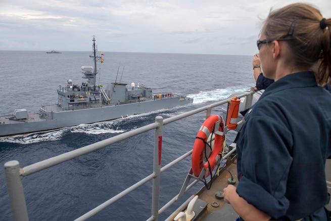A U.S. Navy officer on USS Gunston Hall observes as the ARC Almirante Padilla sails alongside.