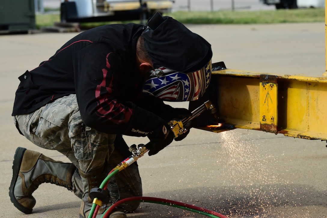 Senior Airman David Corona, a 28th Maintenance Squadron metals technician, cuts off a steel plate with an oxyacetylene torch at Ellsworth Air Force Base, S.D., Aug. 23, 2018. The metals technology shop runs 24-hour operations to provide different metals technologies for all squadrons on base. (U.S. Air Force photo by Airman John Ennis)