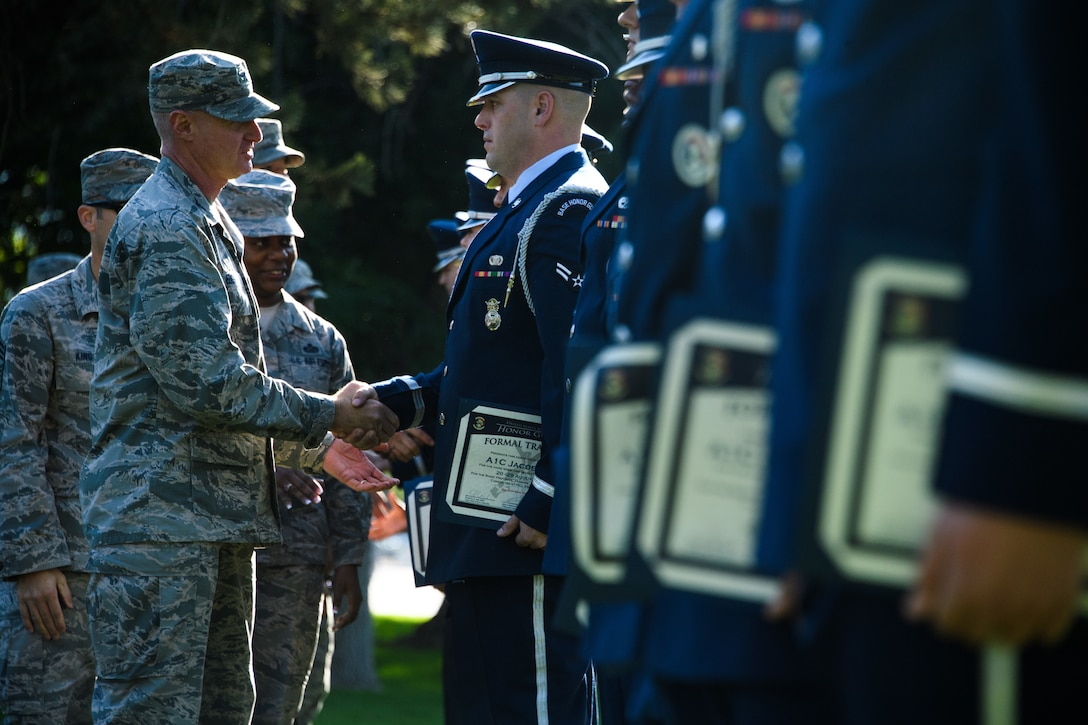 Col. Jon Eberlan, 75th Air Base Wing commander, shakes hands with Airman 1st Class Jacob Faine after an honor guard graduation ceremony at Hill Air Force Base, Utah, Aug. 29, 2018. Twenty Airmen from Hill, F. E. Warren, Mountain Home and Nellis Air Force Bases graduated from the 80-hour course instructed by a U.S. Air Force Honor Guard Mobility Training Team from Joint Base Anacostia-Bolling, Washington D.C. (U.S. Air Force photo by R. Nial Bradshaw)