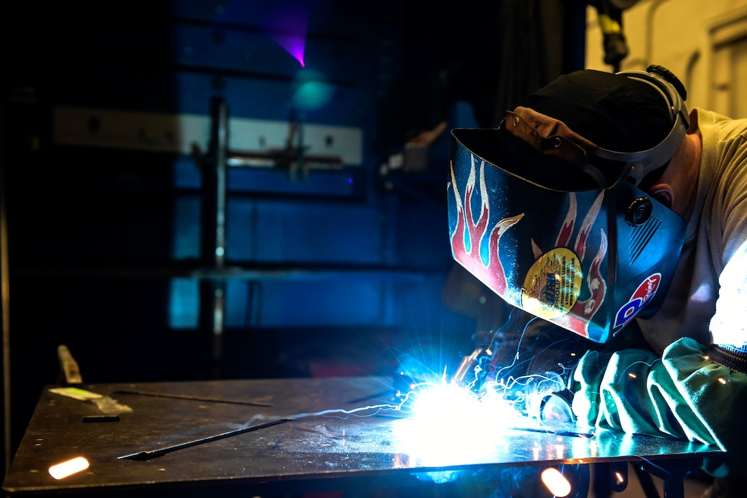 Metals Tech. instructor demonstrates welding to students.