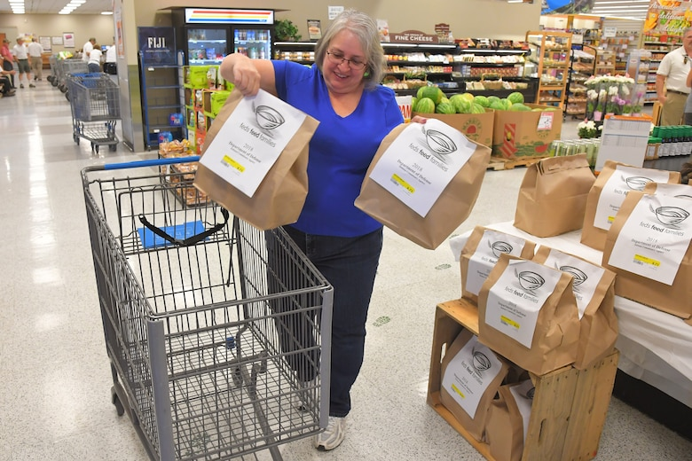 Kim Lingel, patron at the Hill Commissary, participates in the 2018 Feds Feed Families program by purchasing bags of food for donation Sept. 5, 2018, at Hill Air Force Base, Utah. (U.S. Air Force photo by Todd Cromar)