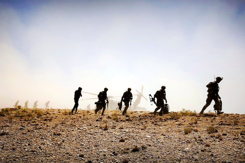 Soldiers patrol the desert after leaving a Black Hawk helicopter.