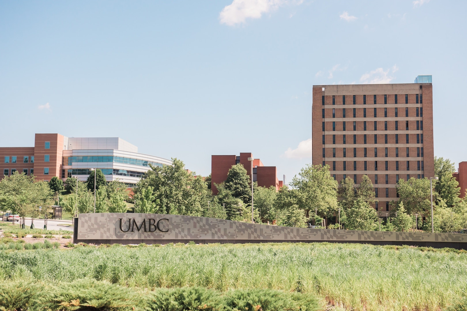 Landscape photo of UMBC sign at entrance to the campus during a sunny day. Three academic buildings are visible behind the sign.
