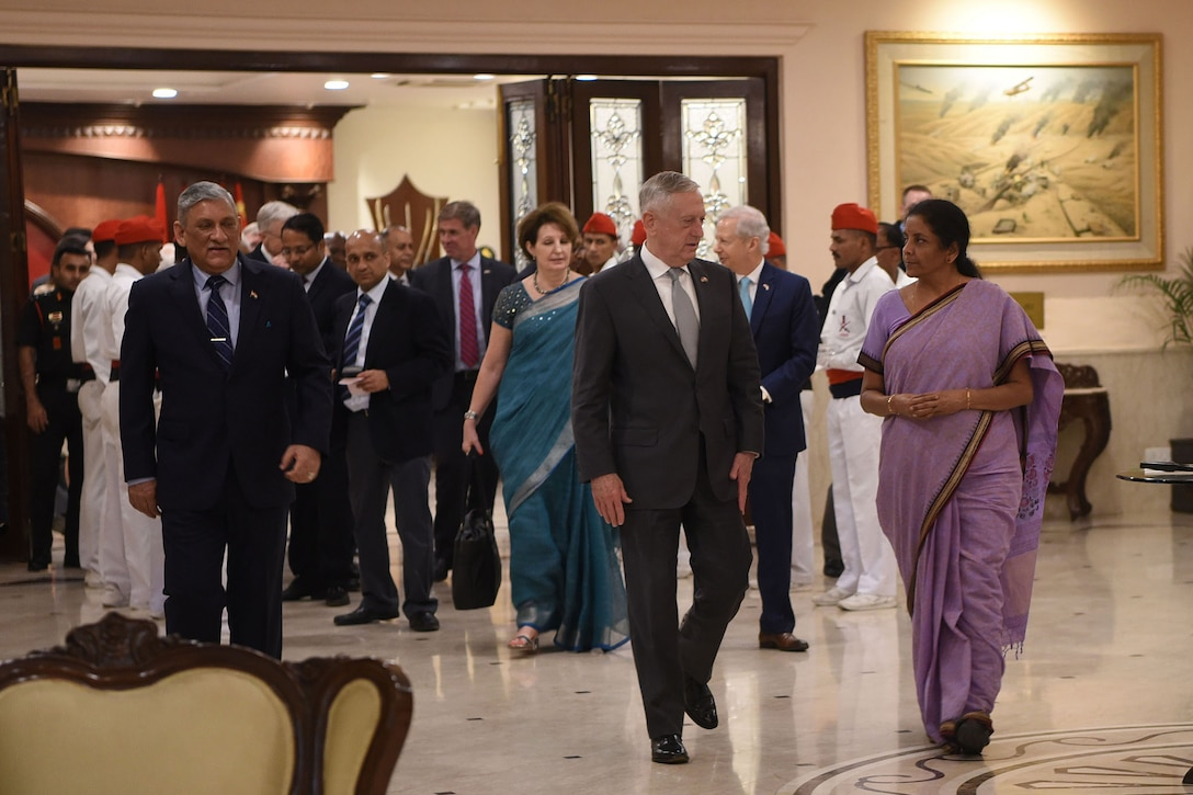 Defense Secretary James N. Mattis walks with Indian Defense Minister Nirmala Sitharaman and a group of people down a hallway.