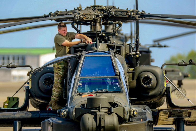 A soldier cleans a helicopter's blades.