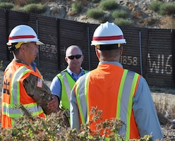 Col. Aaron Barta, U.S. Army Corps of Engineers Los Angeles District commander, left, is briefed about border infrastructure at the San Diego and Mexico International Border during an Aug. 30 project site visit in San Diego County, California.