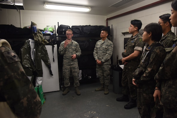 U.S. Air Force Airman 1st Class Garrett Smith, center, 51st Medical Group flight medicine technician, explains the powered air-purifying respirator suit to Republic of Korea Air Force flight technicians and nurses during a tour of the medical group's patient decontamination area at Osan Air Base, Republic of Korea, Sept. 6, 2018. The suit is used to wear to avoid contamination to the skin in a chemical environment. (U.S. Air force photo by Tech Sgt. Ashley Tyler)