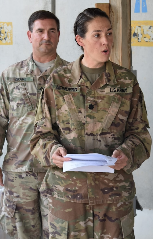 Lieutenant Col. Rachel Honderd, Afghanistan District Deputy Commander reads the history of the DeFleury Medal, as John Drake, Deputy District Engineer for Programs and Project Management Division looks on. The de Fleury medal was named in honor of Francois de Fleury, a French Engineer in the Continental Army.
