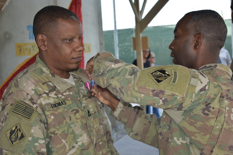 The Superior Civilian Service Award and NATO Medal are presented to Lawrence W. Thomas by Afghanistan District Commander, Col. Jason E. Kelly.