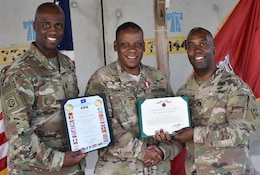 Command Sergeant Major Nathaniel Atkinson and Col. Jason Kelly, Afghanistan District Commander, present the Superior Civilian Award and NATO Medal certificates, along with a handshake to Lawrence W. Thomas, Deputy Chief of Programs and Project Management Division.