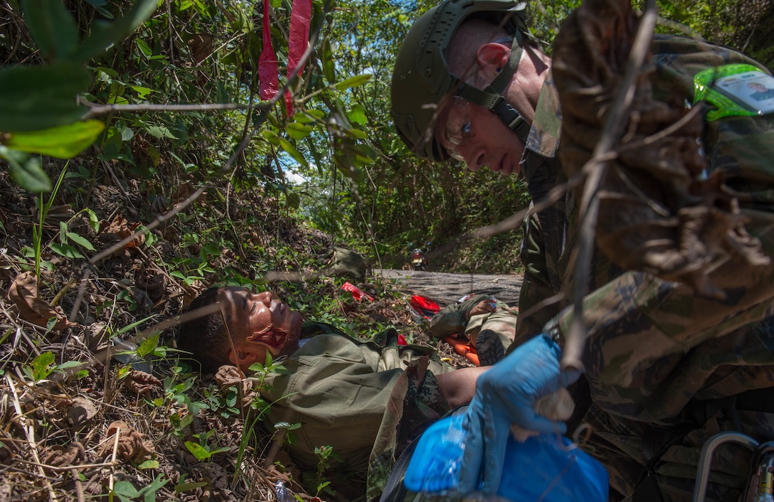 A medic from the Brazilian Air Force provides aid to a triage patient during a simulation as part of the Angel de los Andes exercise Sept. 5, 2018 at German Olano Air Base, Colombia. Airmen from Colombia, Peru, Brazil and the United States worked with Colombian firefighters and civil defense team to air evacuate more than 25 people during a simulated aircraft crash. (U.S. Air Force photo by Staff Sgt. Robert Hicks)
