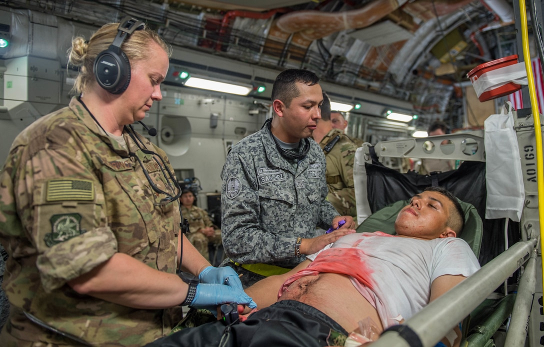 U.S. Air Force and Colombian Airmen work together to simulate providing aid to a triage patient on board a C-17 Globemaster III from Charleston Air Force Base, South Carolina, during exercise Angel de los Andes Sept. 5, 2018 at German Olano Air Base, Colombia. Airmen from Colombia, Peru, Brazil and the United States worked with Colombian firefighters and civil defense team to air evacuate more than 25 people during a simulated aircraft crash. (U.S. Air Force photo by Staff Sgt. Robert Hicks)