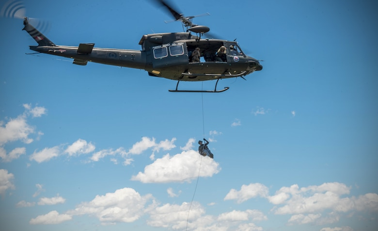 An Airman from the Colombian Air Force rappels from a Peruvian helicopter during exercise Angel de los Andes Sept. 5, 2018 at German Olano Air Base, Colombia. Airmen from Colombia, Peru, Brazil and the United States worked with Colombian firefighters and civil defense team to air evacuate more than 25 people during a simulated aircraft crash. (U.S. Air Force photo by Staff Sgt. Robert Hicks)