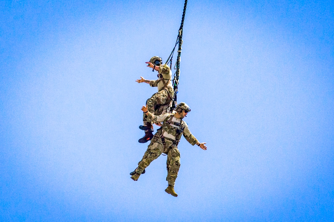 Tactical air control party Airmen with the 227th Air Support Operations Squadron, New Jersey Air National Guard, demonstrate a special extraction system while hanging from a UH-60L Black Hawk helicopter assigned to the 1st Assault Helicopter Battalion, New Jersey Army National Guard, during the 2018 Atlantic City International Airshow at Atlantic City, New Jersey, Aug. 22, 2018. (New Jersey National Guard photo by Mark C. Olsen)