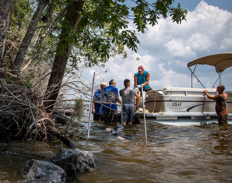 Volunteers from the 823rd Red Horse Squadron and a base housing privatization team unload rocks from a boat for a reef project along the coastline of Eglin Air Force Base, Florida, Aug. 24, 2018. (U.S. Air Force photo by Samuel King Jr.)