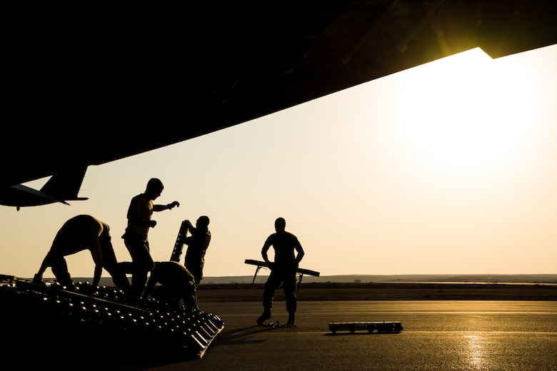 Airmen with the 816th Expeditionary Airlift Squadron and 332nd Air Expeditionary Wing prepare to load cargo on a C-17 Globemaster III at an undisclosed location in Southwest Asia after transporting cargo between U.S. Africa Command and U.S. Central Command, Aug. 28, 2018. (U.S. Air Force photo by Tech. Sgt. Ted Nichols)