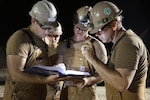 U.S. Navy Seabees review a drilling manual during water well drilling exploration operations in Riohacha, Colombia.