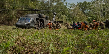 Colombian civil defense team, firefighters and Peruvian Airmen load triage patients onto a Colombian UH-60 Blackhawk