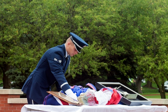 Senior Airman Zachary, Offutt Air Force Base Honor Guard member, lays a wreath and roses next to a piece of C-130 wreckage from 60528, an aircraft which was shot down in the Cold War, during a remembrance ceremony held Aug. 30, 2018, at Offutt Air Force Base, Nebraska. The ceremony was attended by members of the 97th Intelligence Squadron, the Prop Wash Gang, a group of retired ISR operators, family members and fellow wingman to the fallen. (U.S. Air Force photo by L. Cunningham)