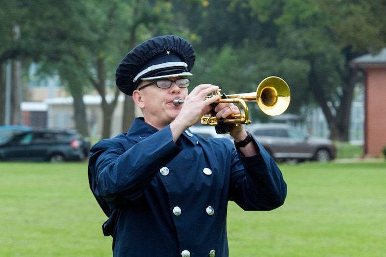 """U.S. Air Force Staff Sgt. Daniel Thrower, Heartland of America Band hornist, plays """"Taps,"""" during the 60528 Remembrance Ceremony Aug. 30, 2018, at Offutt Air Force Base, Nebraska. The ceremony was held to honor the 17 crewmembers who were lost during the Cold War when their C-130, which was modified to fly reconnaissance missions, was shot down. The aircraft's tail number was 60528. (U.S. Air Force Photo by L. Cunningham)"""