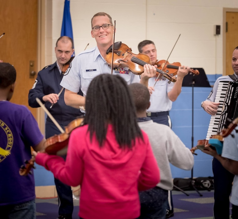 Master Sgt. Luke Wedge performs during a strings clinic at a local school