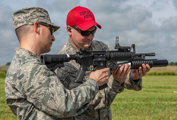 Staff Sgt. Nathan Minick, 375th Security Forces Squadron combat arms trainer, right, teaches a participant how to re-load a M203 40mm grenade launcher during the Non-Lethal Weapons Familiarization event Aug. 30, 2018, at the Illinois National Guard Training Area in Sparta, Illinois.