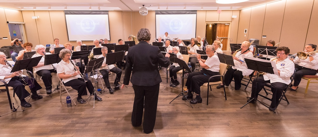 WAF Band historian Jeananne Nichols conducts the WAF Band and current US Air Force Band members during a concert at the Armed Forces Retirement Home in Washington, D.C.