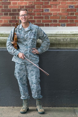 Master Sgt. Luke Wedge poses in front of Historic Hangar 2, Home of the U.S. Air Force Band