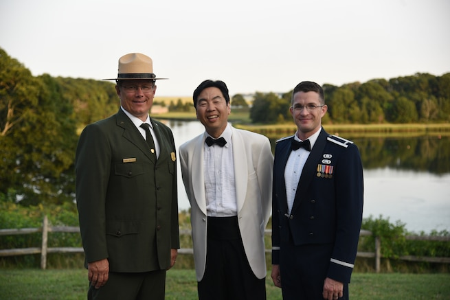 Lt. Philip Emory poses with the conductor of the Cape Symphony Mr. Jung-Jo Park and Cape Cod National Seashore Superintendent Brian Carlstrom