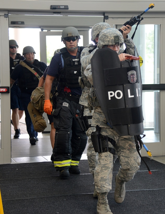 The 72nd Security Forces personnel lead a team of Tinker firefighters in the building to assess and help the wounded victims.