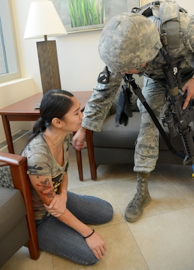 A member of the 72nd Security Forces Squadron speaks to a victim to quickly check the severity of her wounds and to ask for any pertinent information she may have about an active shooter during an Aug. 15 exercise in the 72nd Medical Group.