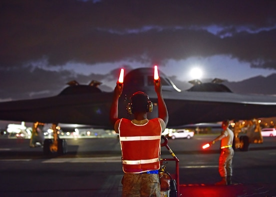 U.S. Air Force Airman 1st Class Christopher Rucker, a crew chief assigned to the 509th Aircraft Maintenance Squadron, marshals a B-2 Spirit returning from a routine training mission at Joint Base Pearl Harbor-Hickam, Hawaii, Sept. 6, 2018.