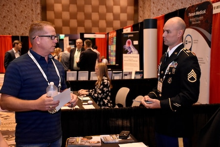Staff Sgt. Jacob D. Varvel, U.S. Army health care recruiter, speaks with an attendee of the PAINWeek 2018 conference at The Cosmopolitan of Las Vegas. Varvel, from the Mountain Region Physician Recruiting Station, was on hand with other representatives from the Las Vegas Medical Recruiting Station and the 6th Medical Recruiting Battalion to promote the benefits and opportunities of a career in Army Medicine. For more information on the Army's more than 90 medical specialties go to healthcare.goarmy.com. (U.S. Army Photo by Andrew Lynch)