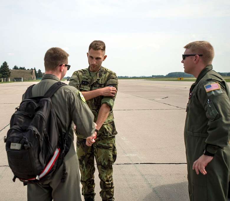 Staff Sgt. Matthew Parker, in-flight refueling specialist, 155th Air Refueling Wing, Nebraska Air National Guard, exchanges patches with grounds service technician assigned to Pardubice Air Base, Czech Republic, with 1st Lt. Taylor Ashmore, 155th ARW mission pilot, after a refueling flight during a joint training exercise in the Pardubice Region. This year the State of Nebraska, and the State of Texas, are celebrating the 25th year of their partnership with the Czech Republic through the State Partnership Program (SPP). The ANG has 73 partnerships around the world to promote access, enhance military capabilities, improve interoperability, and enhance the principles of responsible governance. (U.S. Air National Guard photo by Tech. Sgt. Rana Franklin)