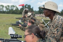 A U.S. Marine Corps primary marksmanship coach, with Marksmanship Training Company, Weapons and Field Training Battalion, supervises a recruit during Table 1 at Chosin range on Marine Corps Recruit Depot, Parris Island, S.C., Sept. 5, 2018. Marine recruits spend a week learning the fundamentals of marksmanship and apply it the following week in Table 1.