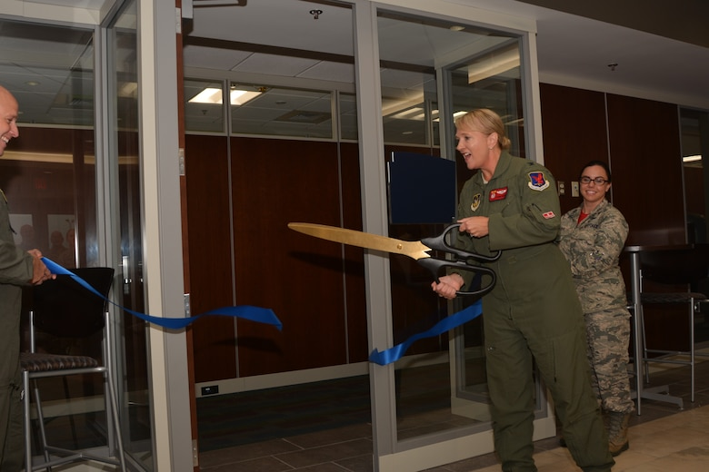 """With a quick motion of oversized scissors, Col. Laurie Dickson, Commander, 513th Air Control Group, officially """"opens"""" the new 513th ACG headquarters for business Sept. 7, 2018, at Tinker Air Force Base, Oklahoma. The 513th Air Control Group is the only Air Force Reserve unit to fly and maintain the E-3 Sentry, an Airborne Warning and Control System aircraft that provides surveillance, warning and tactical control of U.S. and allied military aircraft.  As a Reserve associate unit, Airmen assigned to the 513th ACG work hand-in-hand with the active-duty 552nd Air Control Wing, which is responsible for the E-3 Sentry aircraft assigned to Tinker AFB. Working together, Tinker AFB's Team AWACS maintains a reliable presence in numerous missions worldwide. (Air Force photo by Master Sgt. Grady Epperly)"""