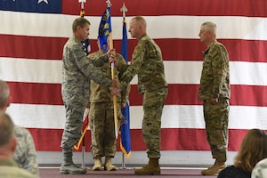 Col. Darrin Anderson, the 119th Wing commander, left, presents the 219th Security Forces Squadron unit flag guidon to Maj. Greg Goodman as Goodman assumes command in a symbolic gesture with the flag representing the squadron command of the 219th Security Forces Squadron at the Minot Air Force Base, N.D., Sept. 8, 2018.