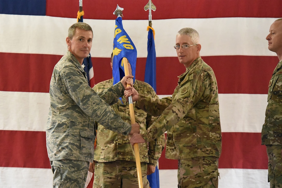 Col. Darrin Anderson, the 119th Wing commander, left, accepts the 219th Security Forces Squadron squadron flag guidon from Lt. Col. Tad Schauer in a symbolic gesture with the flag representing the organizational command of the 219th Security Forces Squadron, with Schauer relinquishing command of the squadron at the Minot Air Force Base, N.D., Sept. 8, 2018.