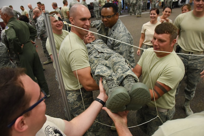 Members of the 118th Wing participate in a team building project during their annual training held at the Air Dominance Center in Savannah, Ga. Aug. 16, 2018. The members were tasked with getting all their team mates through the netting without touching it. (U.S. Air National Guard photo by Master Sgt. Jeremy Cornelius)