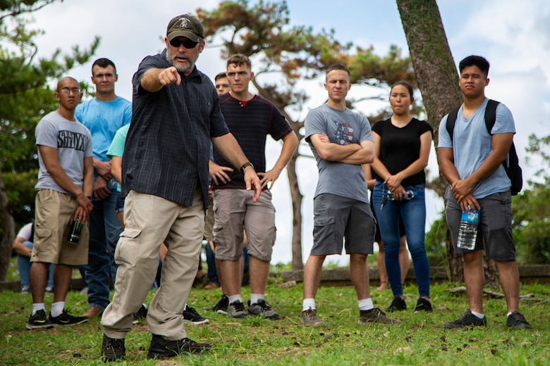 Chris Majewski, a tour guide, points to a Japanese offensive position during a tour Sept. 7, 2018 at Hacksaw Ridge, Okinawa, Japan. Marines and Sailors with Headquarters Company, Headquarters Regiment, 3rd Marine Logistics Group, participated in the World War II battle site tour to learn about the U.S. Marine Corps' history on Okinawa and remember those who have gone before them. Majewski is a tour guide with Marine Corps Community Services Tours+ and is a native of Boulder City, Nevada. (U.S. Marine Corps photo by Pfc. Terry Wong)