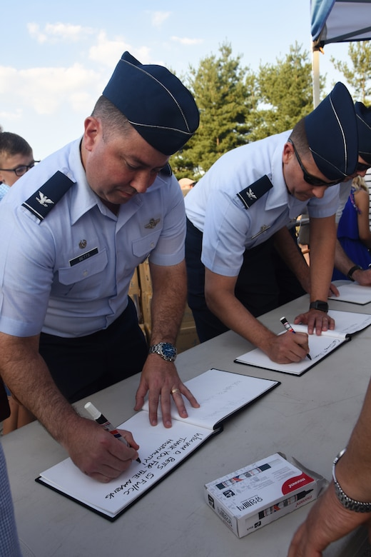 U.S. Air Force Col. William Betts, 51st Fighter Wing Commander, left, and Col. James Vinson, 51st Maintenance Group commander, sign the guest log before the opening ceremony of the 15th annual Korean-American Friendship Cultural Festival at the Songtan Entertainment District, Republic of Korea, Sept. 8, 2018. The festival features Korean folk plays, events and food along with U.S. military personnel residing in South Korea. (U.S. Air Force photo by Tech Sgt. Ashley Tyler)