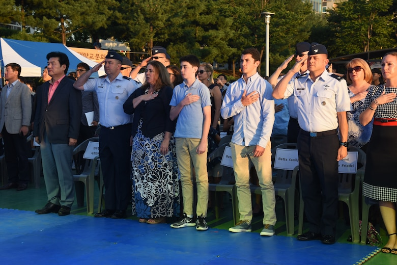 From left, National Assembly Of South Korea member Won Yoo Chul, U.S. Air Force Col. William Betts, 51st Fighter Wing commander and his family, and Col. Jesse Friedel, 51 FW vice commander and his family, pay respects to the U.S. flag during the playing of the American National Anthem before the start of the 15th annual Korean-American Friendship Cultural Festival at the Songtan Entertainment District, Republic of Korea, Sept. 8, 2018. The two-day event was held to help both cultures learn about each other and reinforce U.S. and ROK bond. (U.S. Air Force photo by Tech Sgt. Ashley Tyler)