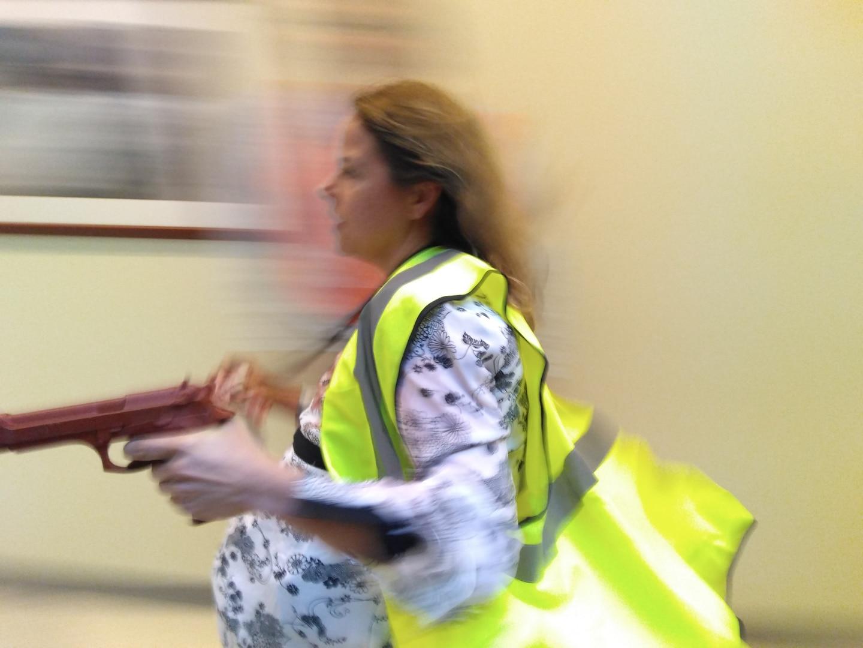Woman running, holding faux handgun, in bright green safety vest