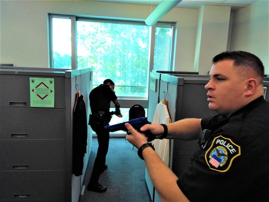 Police officers with mock guns drawn in office suite