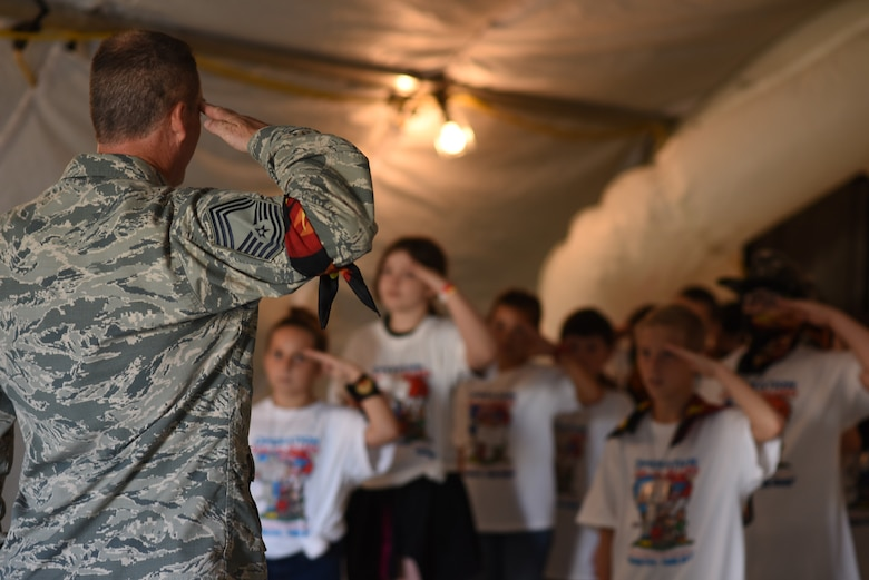 Chief Master Sgt. Richard Beard, 145th Aircraft Maintenance Squadron superintendent, teaches a group of nine to ten year-olds how to salute during the Annual North Carolina (NC) Operation Kids on Guard held at the NC Regional Training Site in Stanly County, Sept. 8, 2018. Children of military members were able to join in activities including short aircraft rides, engaging with military members while learning flight structure and commands, interactive displays with a C-17 Globemaster III and other aircraft, as well as a ropes course and bouncy castles.