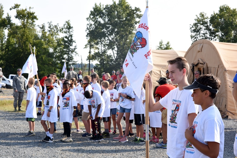 More than sixty children of North Carolina (NC) Air National Guardsmen were lined up in flights by age group awaiting the opening ceremonies of the Annual NC Operation Kids on Guard held at the NC Regional Training Site in Stanly County, Sept. 8, 2018. Children of military members were able to join in activities including short aircraft rides, engaging with military members while learning flight structure and commands, interactive displays with a C-17 Globemaster III and other aircraft, as well as a ropes course and bouncy castles.