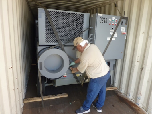 DLA Disposition Services employees ensure carts are secure inside shipping containers for a safer shipment.