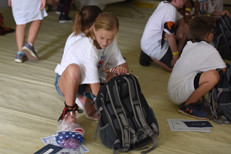 Children of North Carolina (NC) Air National Guardsmen were given backpacks filled with military memorabilia and donated gifts following the Annual NC Operation Kids on Guard held at the NC Regional Training Site in Stanly County, Sept. 8, 2018. Children of military members were able to join in activities including short aircraft rides, engaging with military members while learning flight structure and commands, interactive displays with a C-17 Globemaster III and other aircraft, as well as a ropes course and bouncy castles.