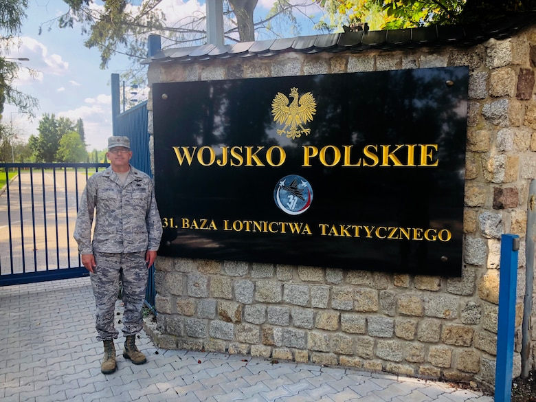 U.S. Air Force Maj. John C. Thompson, 145th Mission Support Group, poses in front of the 31st Tactical Air Base sign during the Deployable Air Base System exercise in Poznan-Krzesiny, Poland, July 30, 2018. Major Thompson spent the majority of July and August in Poland as the exercise commander of the new Deployable Air Base System. It is new concept for the U.S. Air Force and enables the military to respond to potential contingency needs more rapidly.enables the military to respond to potential contingency needs more rapidly.